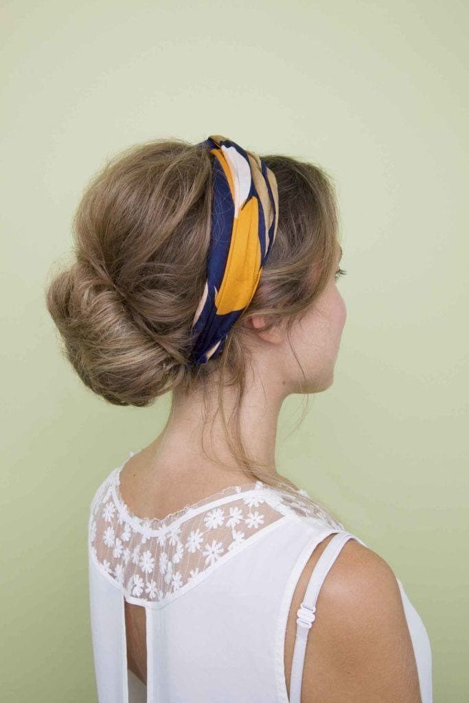 Party hairstyles: Woman with dark blonde straight hair in low bun updo with blue and yellow headband scarf wearing a white top.