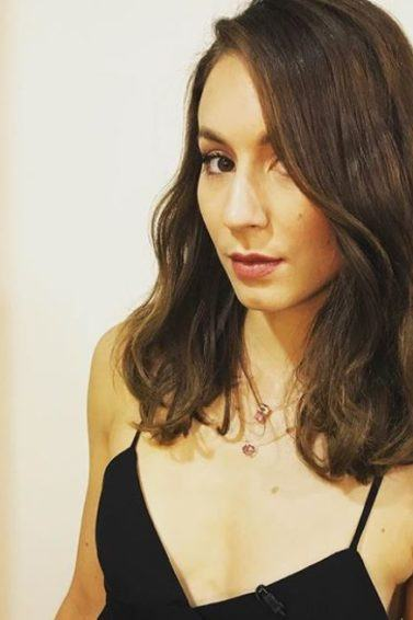 front angled view of Troian Bellisario with medium length brown wavy hair in side parting