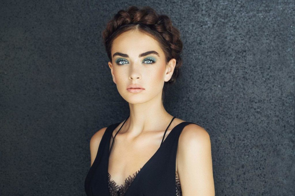 Party hairstyles: Woman with dark brown straight hair in milkmaid braided updo with black vest.