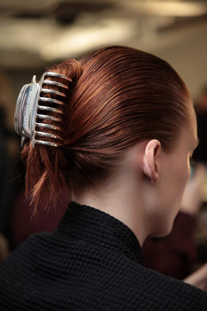 back view of model with auburn hair in updo with hair claw backstage at fashion week