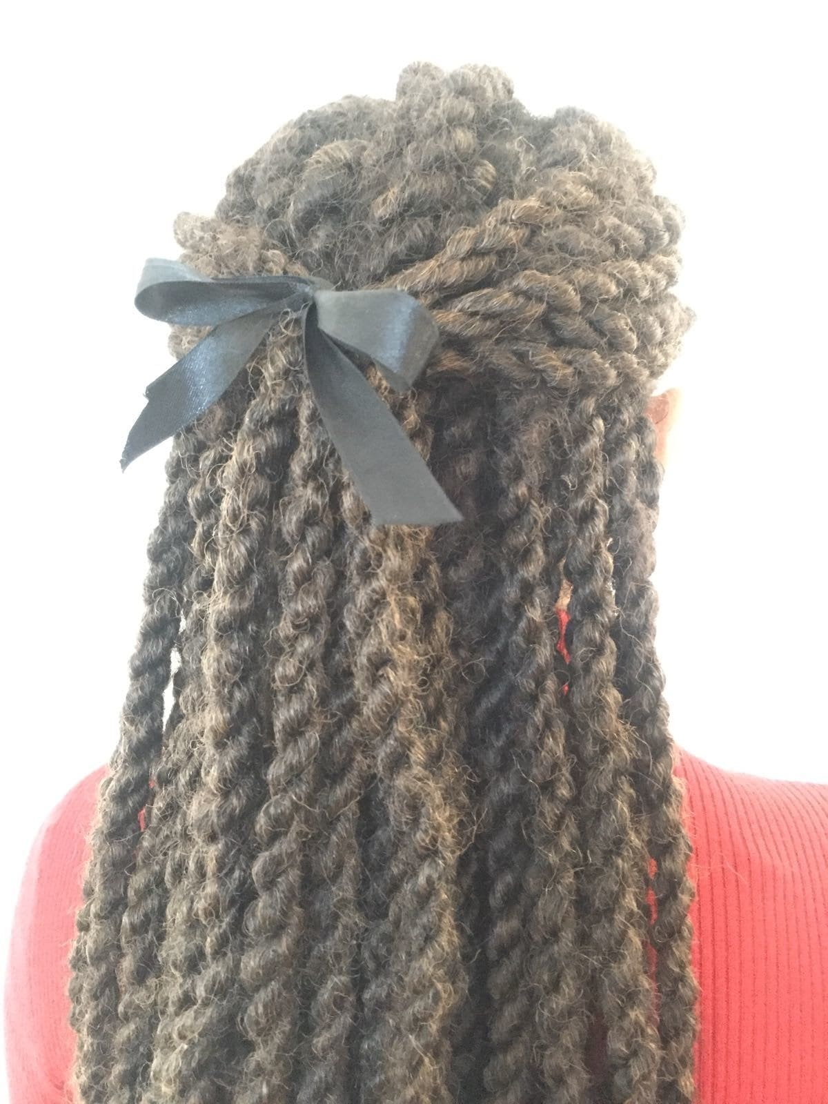 backshot of woman with half up half down marley twist hairstyle that has a bow in it, wearing red jumper