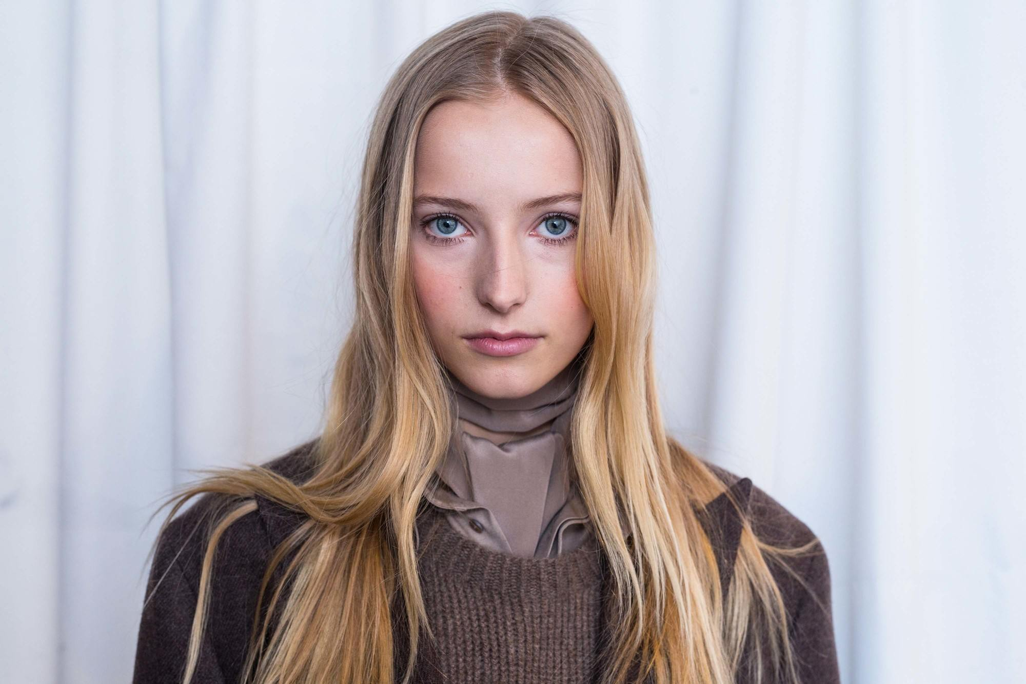 close up shot of model with blonde balayage hair colour, wearing brown outfit