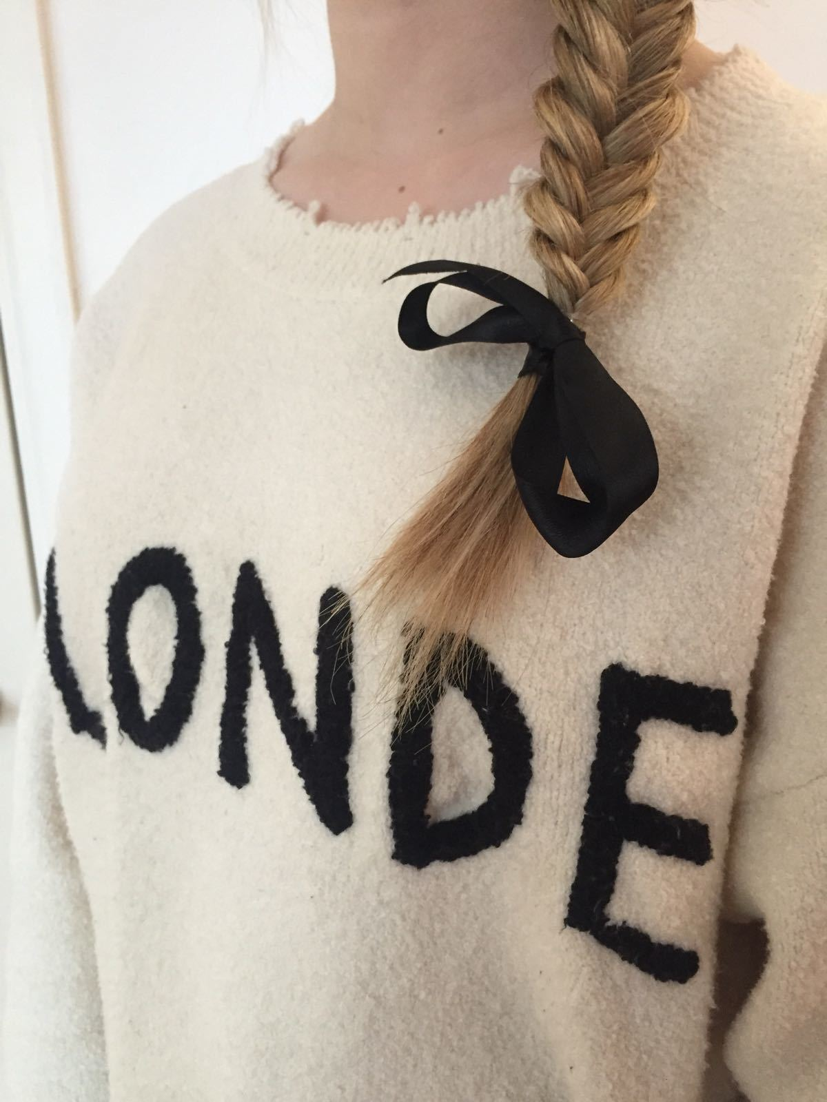 close up shot of woman with blonde hair styled into a side fishtail braid with a bow accessory on it, wearing a jumper that says blonde on it
