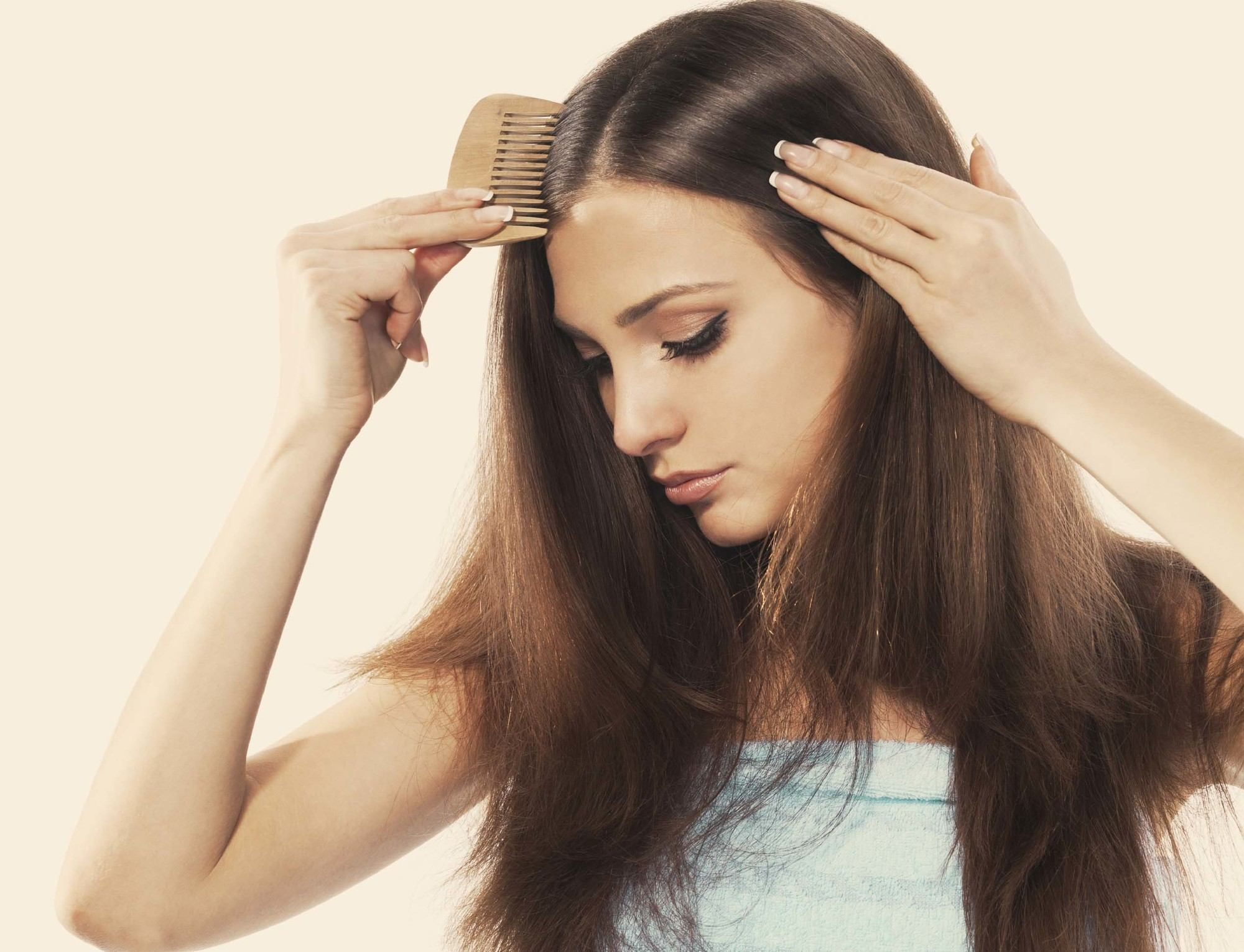 Flat hair solutions girl with long brunette hair holding a comb to her head