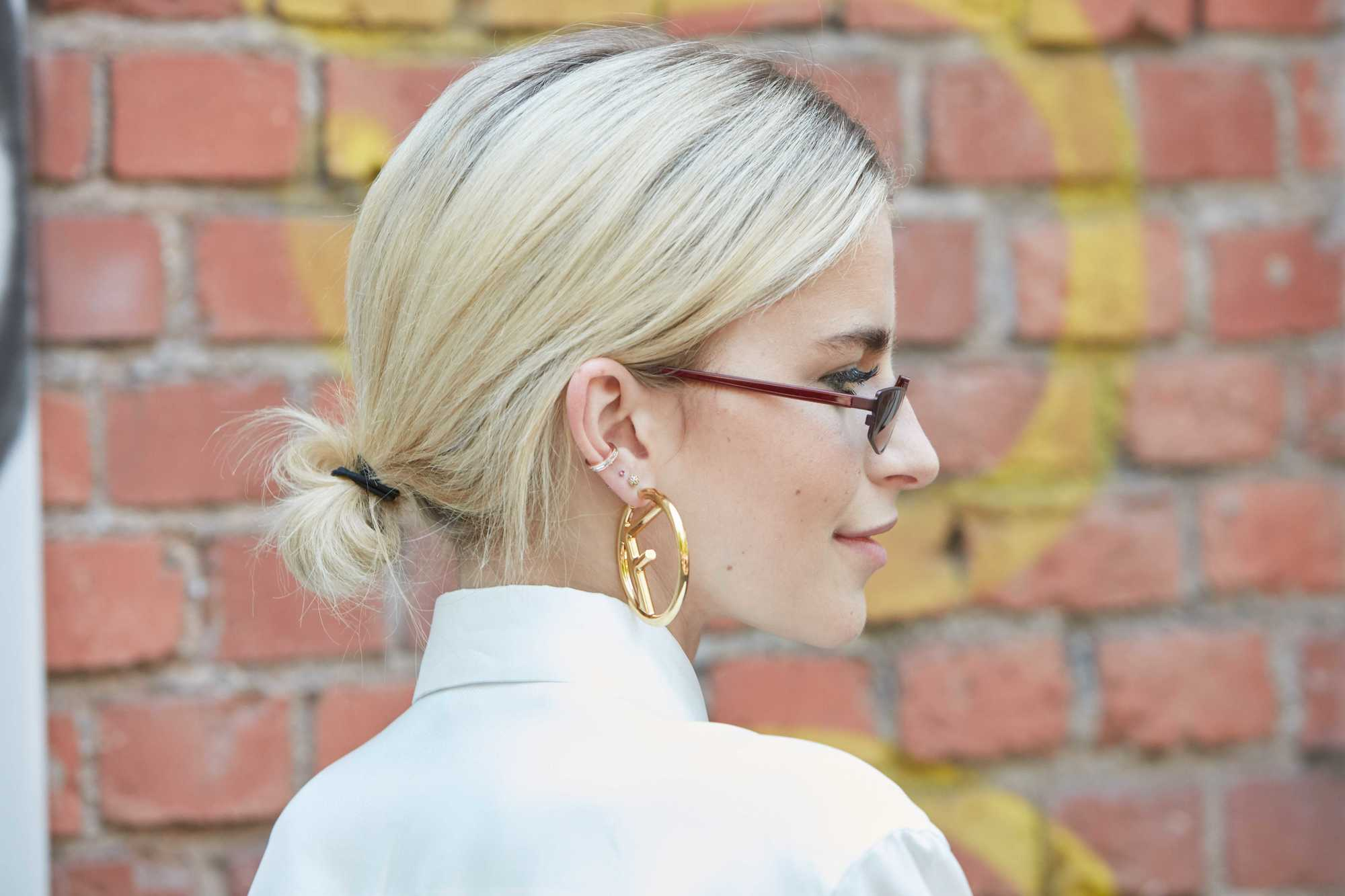 How to style thin hair: Caroline Daur with her platinum blonde short and fine hair styled into a low bun, wearing white shirt and hoop earrings on the street
