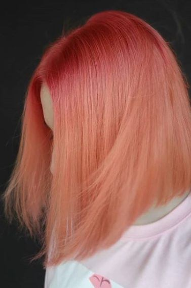 Pantone's Colour of the Year 2019: Close-up of a woman with an angled bob in coral pink ombre, wearing a baby pink t-shirt standing against a black backdrop