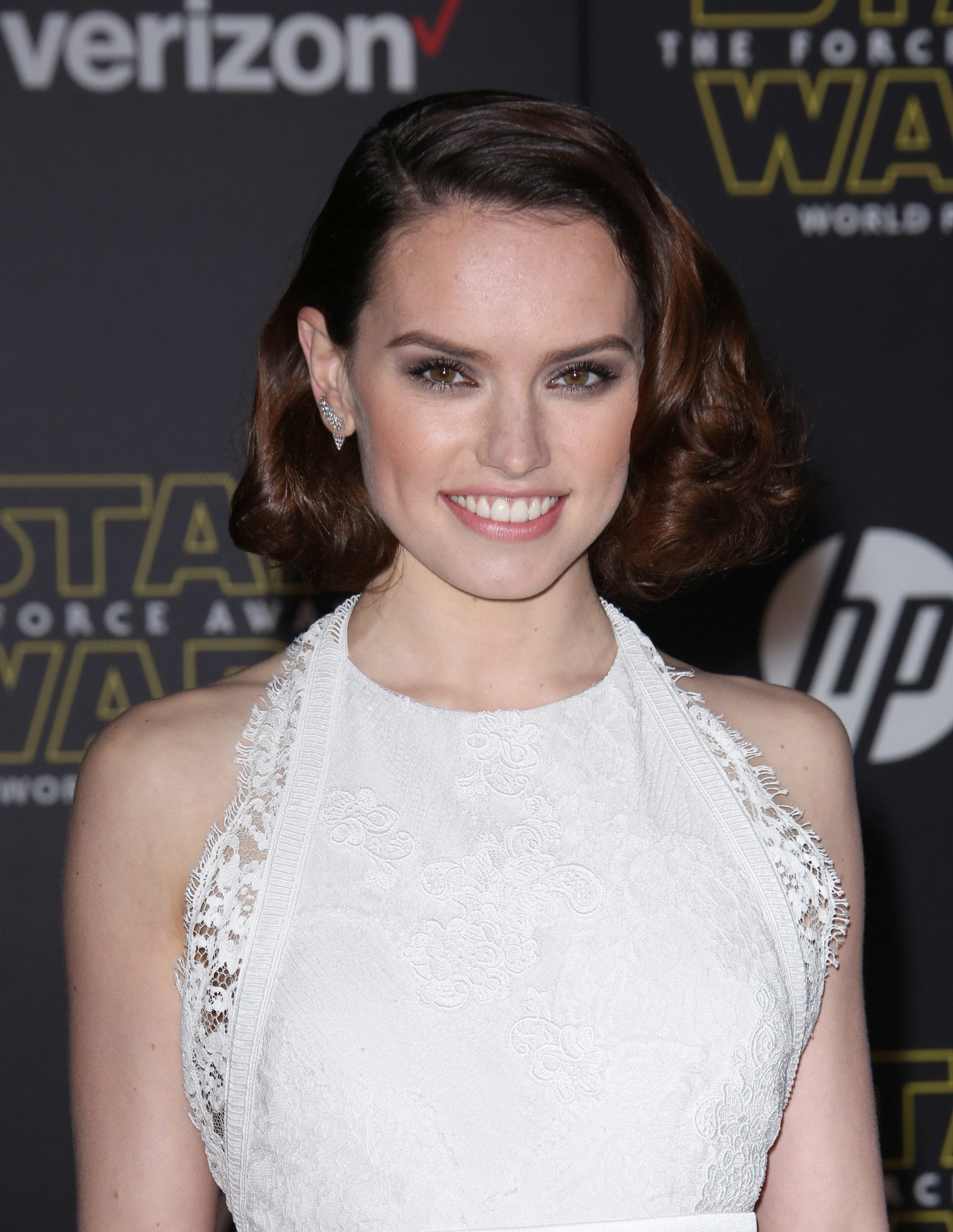 front view of daisy ridley with side parted hollywood waves shoulder length red carpet hairstyle