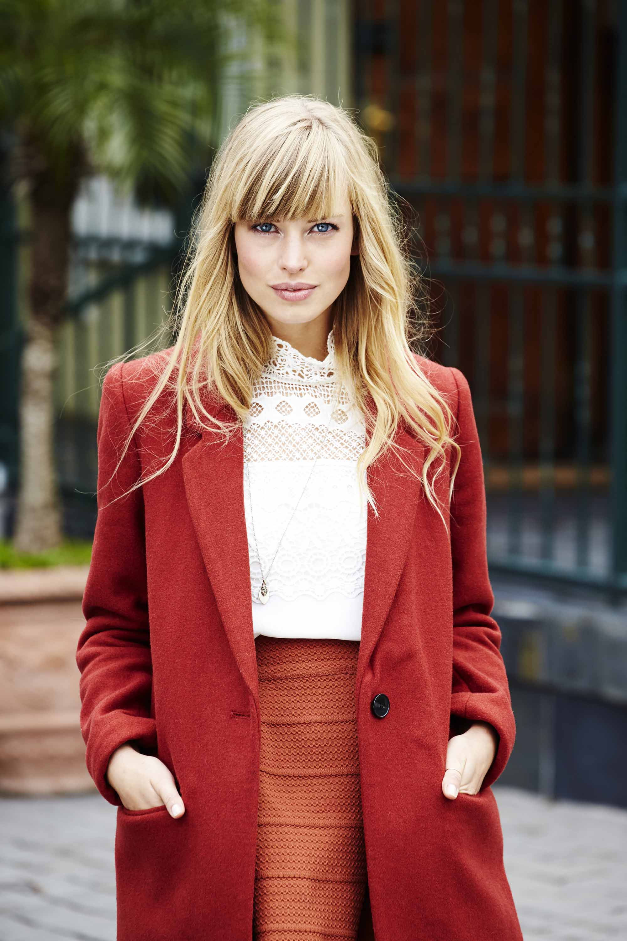 Flat hair solutions blonde woman with side fringe in red coat smiling