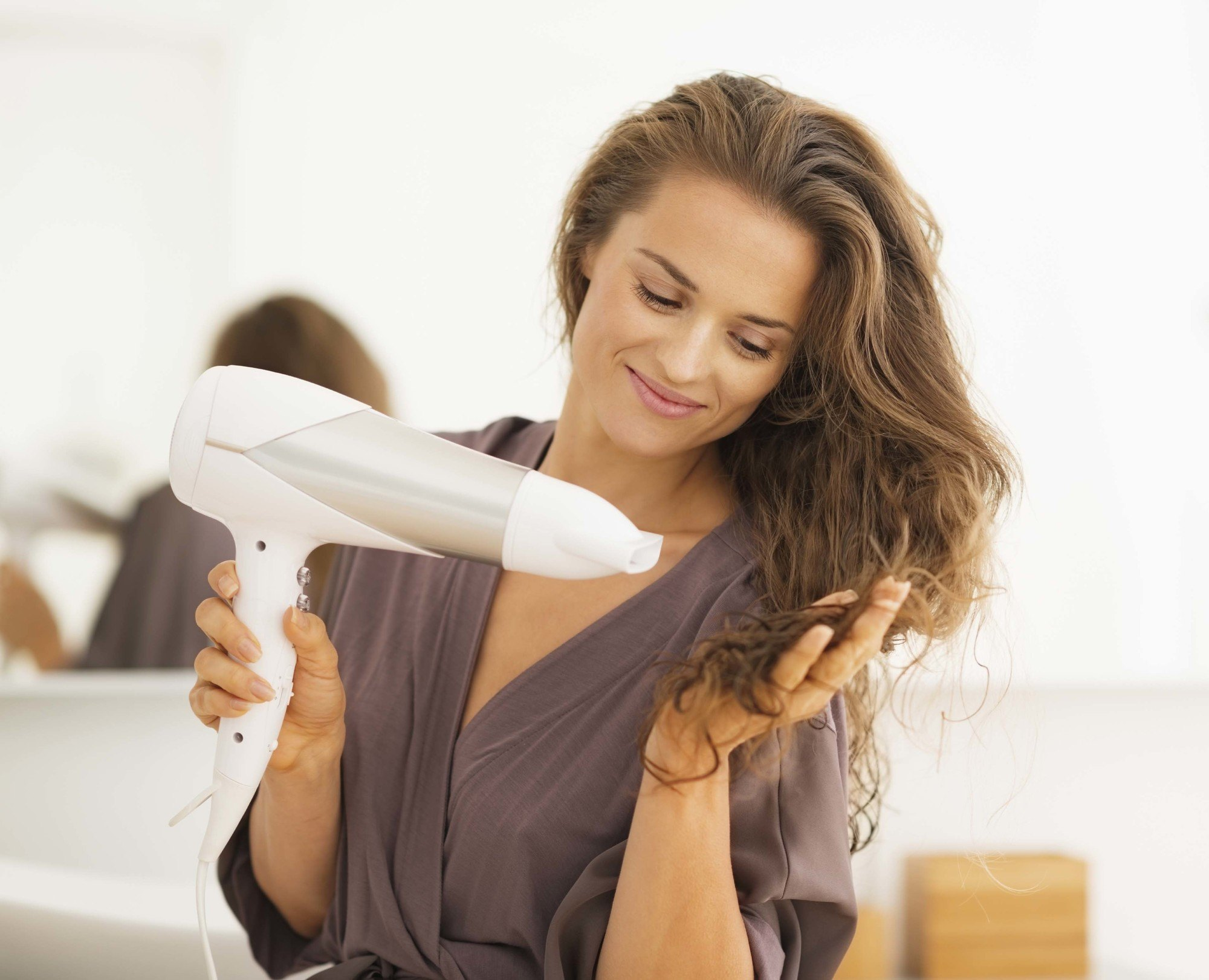 Flat hair solutions woman with hair dryer drying brunette hair and smiling