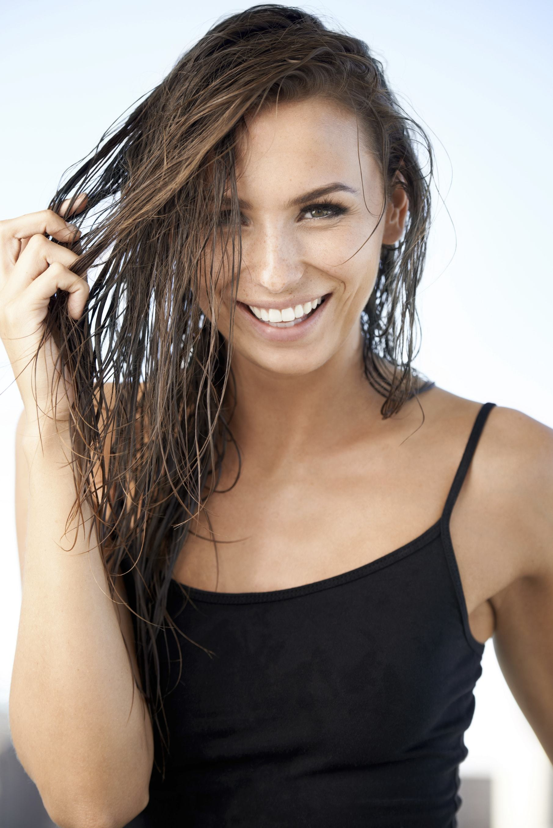 Flat hair solutions woman smiling into the camera with wet hair
