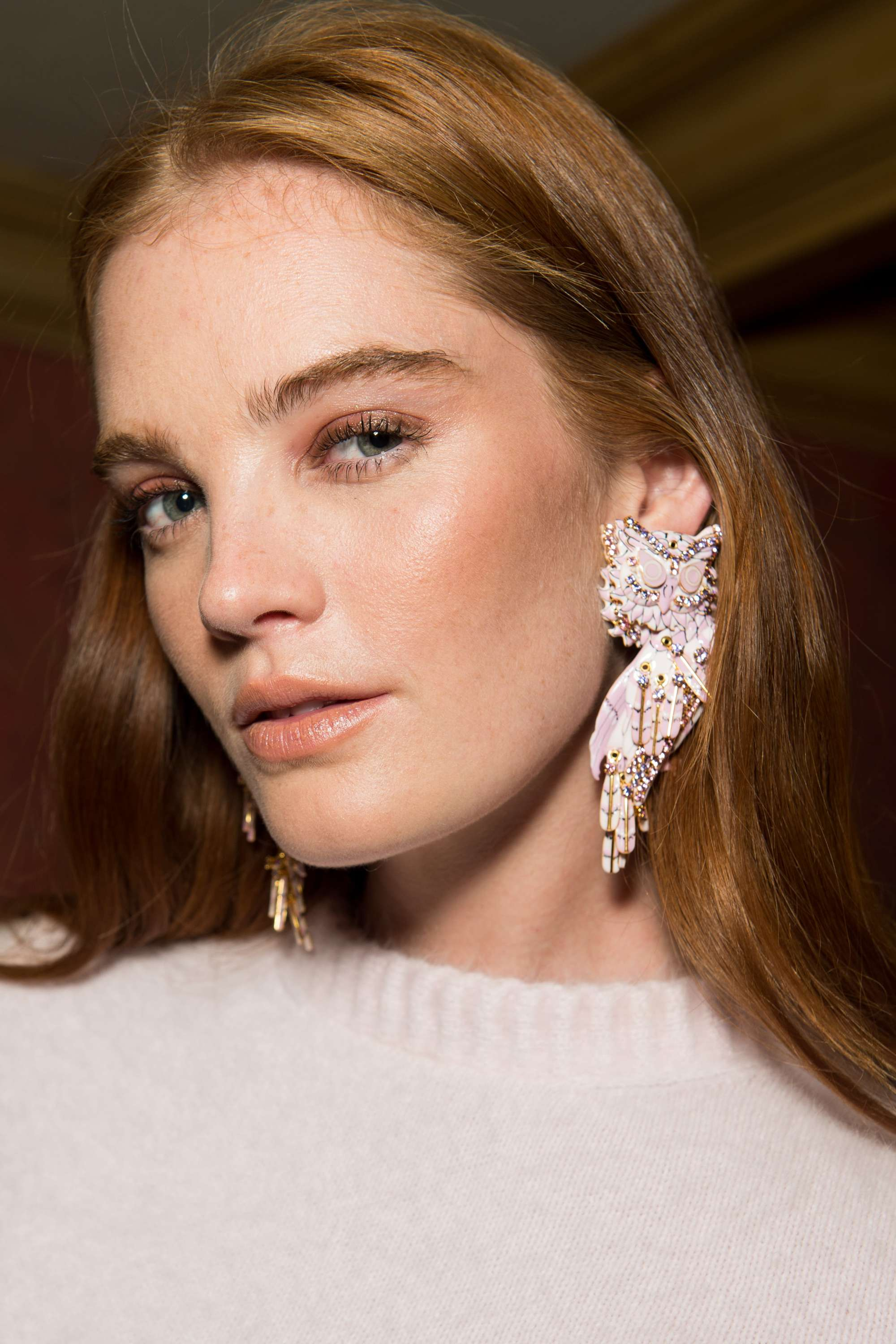 close up shot of model with shiny hair, wearing party makeup, earrings and white jumper
