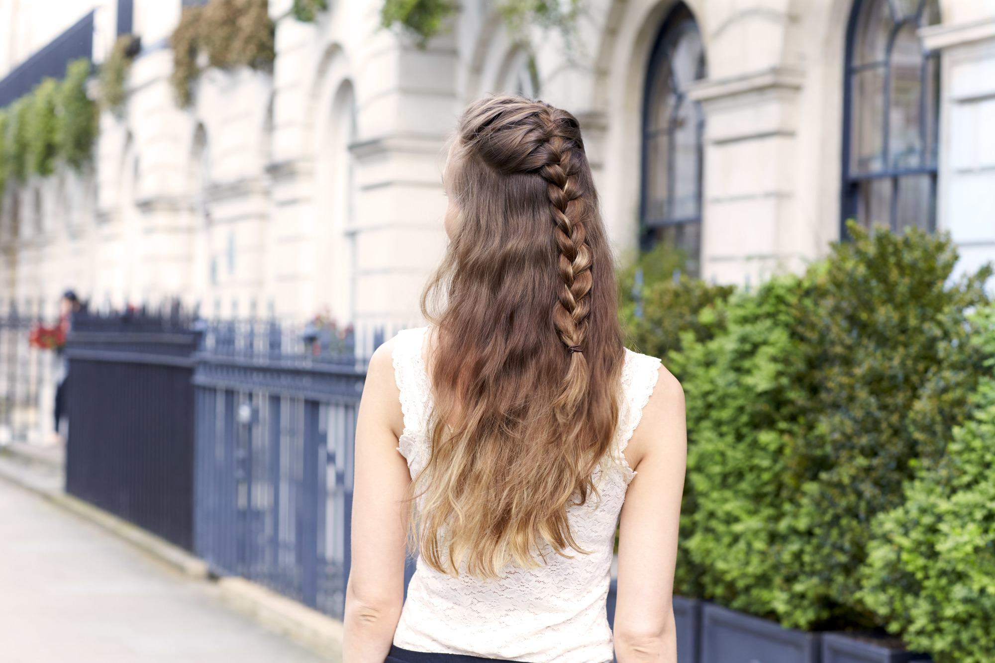 Flat hair fixes woman with braid and curls on street with long brunette hair