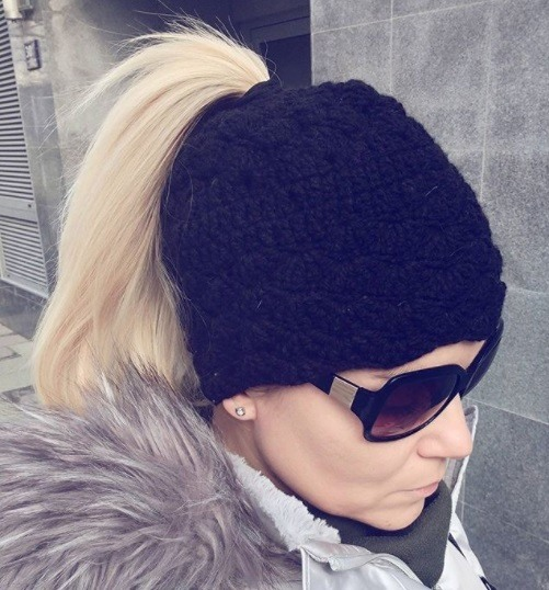 Blonde woman with her hair in a ponytail with a black crochet headband hat