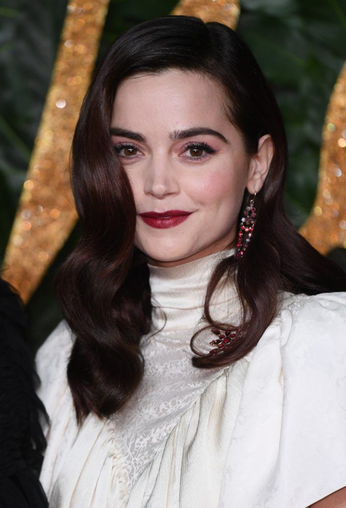 The Fashion Awards 2018: Jenna Coleman with her dark brunette hair in sideswept old Hollywood glamour curls, wearing a white high neck Victoriana dress