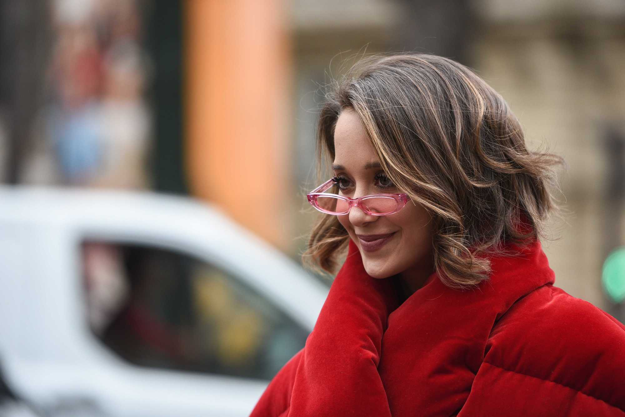 Lana El Sahely with short caramel brown hair styled into loose curls, wearing micro sunglasses and a red velvet jacket, posing on the street