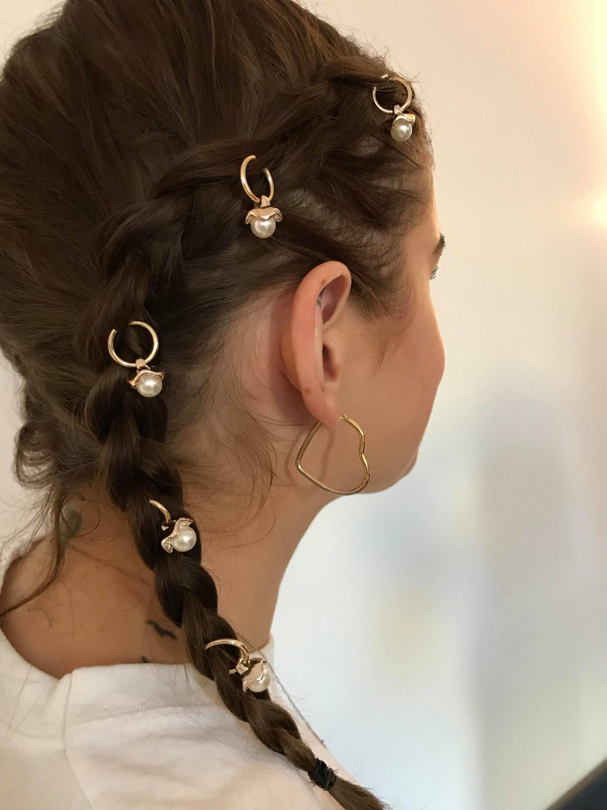 all things hair editor leona with her hair in double dutch braids with pearl embellished hair rings and heart shaped gold earrings