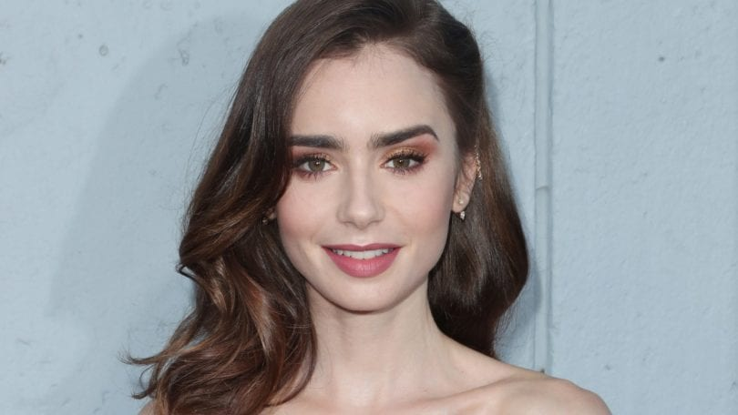 close up shot of lily collins with dark brown hair, fashioned into vintage waves, wearing red dress on red carpet