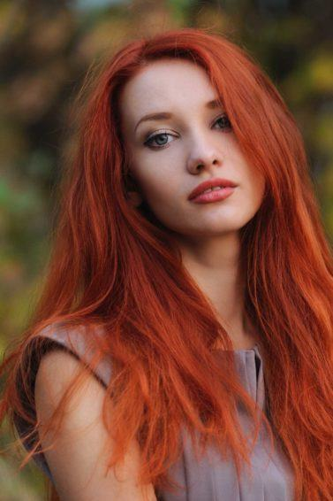 woman outdoors with long bright red dyed hair