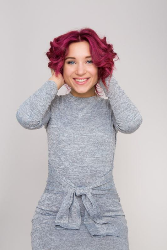 How to make short hair wavy girl with red hair smiling at camera in grey dress