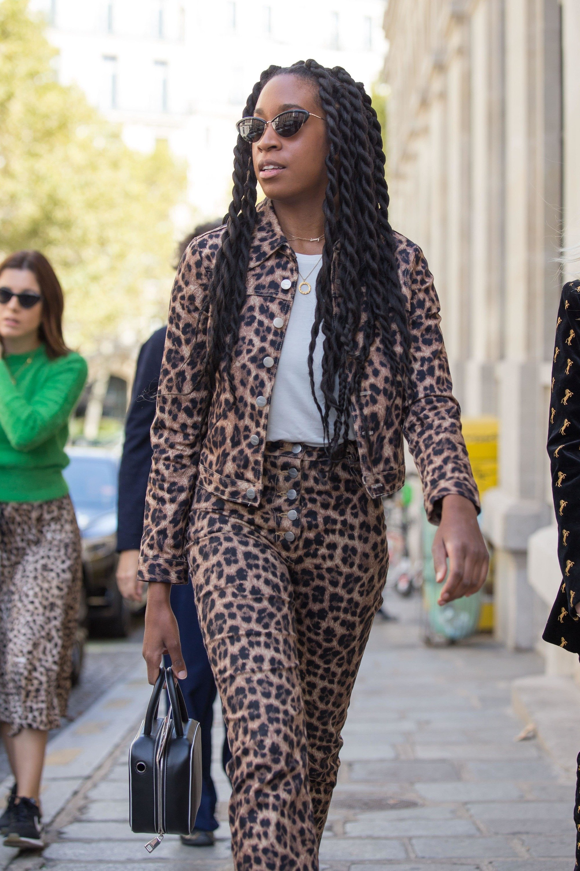 Chrissy Ford with marley twists on the street at fashion week, wearing leopard print with sunglasses while walking