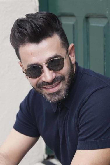 the best mens hair products: close up shot of man with a dark quiff, wearing a blue top and sunglasses, posing outside for spfw