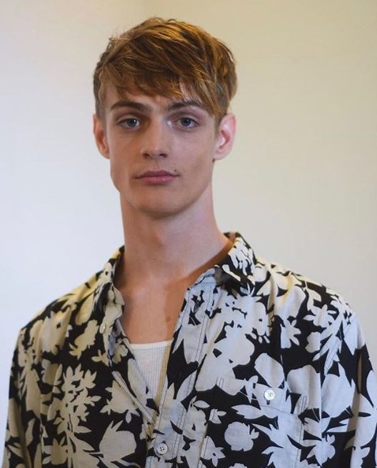 Hairstyles for men with thin hair: Model with blonde hair short sides and long messy top wearing a bold floral shirt.