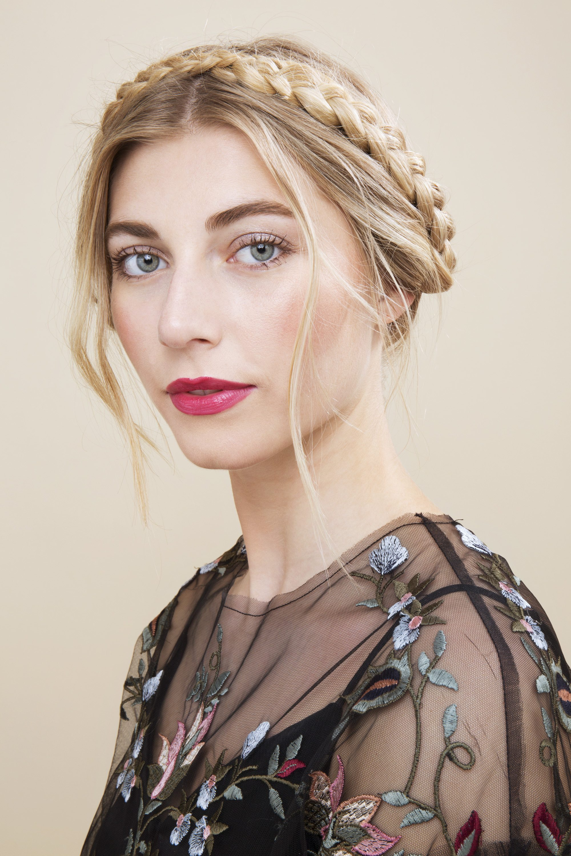 blonde model with hair in milkmaid braids and loose tendrils falling around hairline