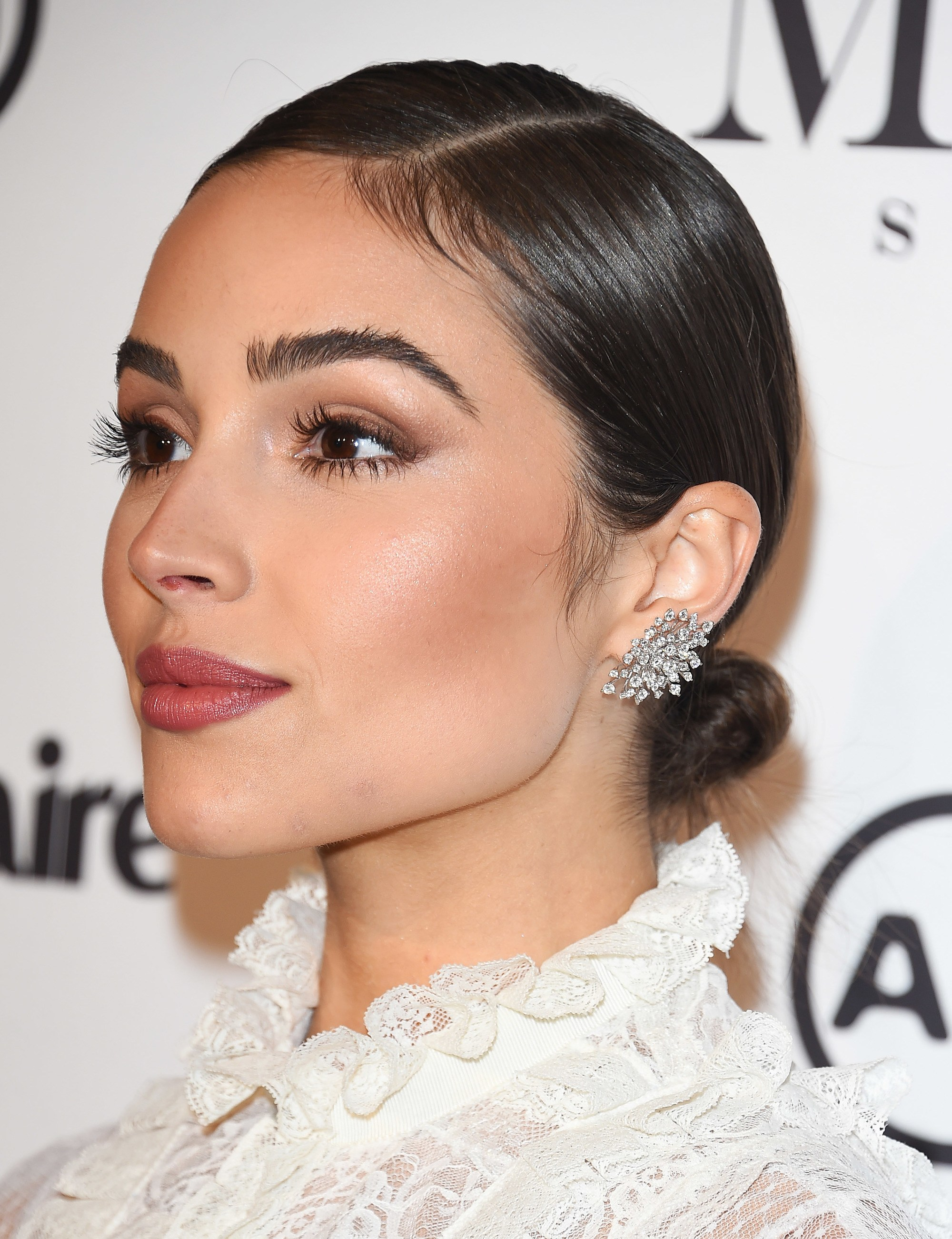 Formal hairstyles for short hair: Close-up of Olivia Culpo with dark glossy short hair in a side-parted low mini bun