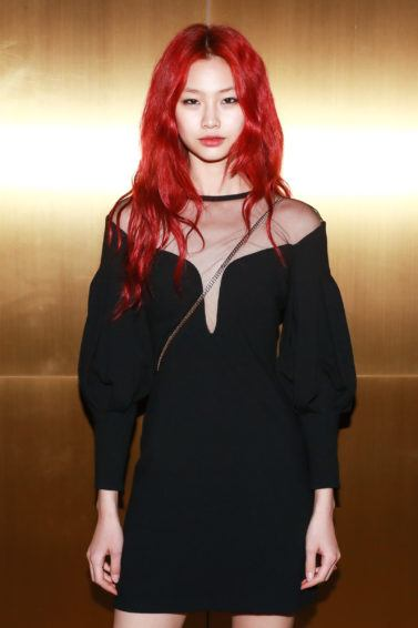 Close up shot of model with red hair, wearing black dress and posing against golden wall