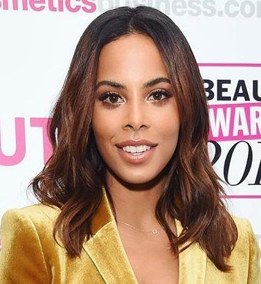 close up shot of rochelle humes with straight wavy hair, wearing yellow velvet jacket