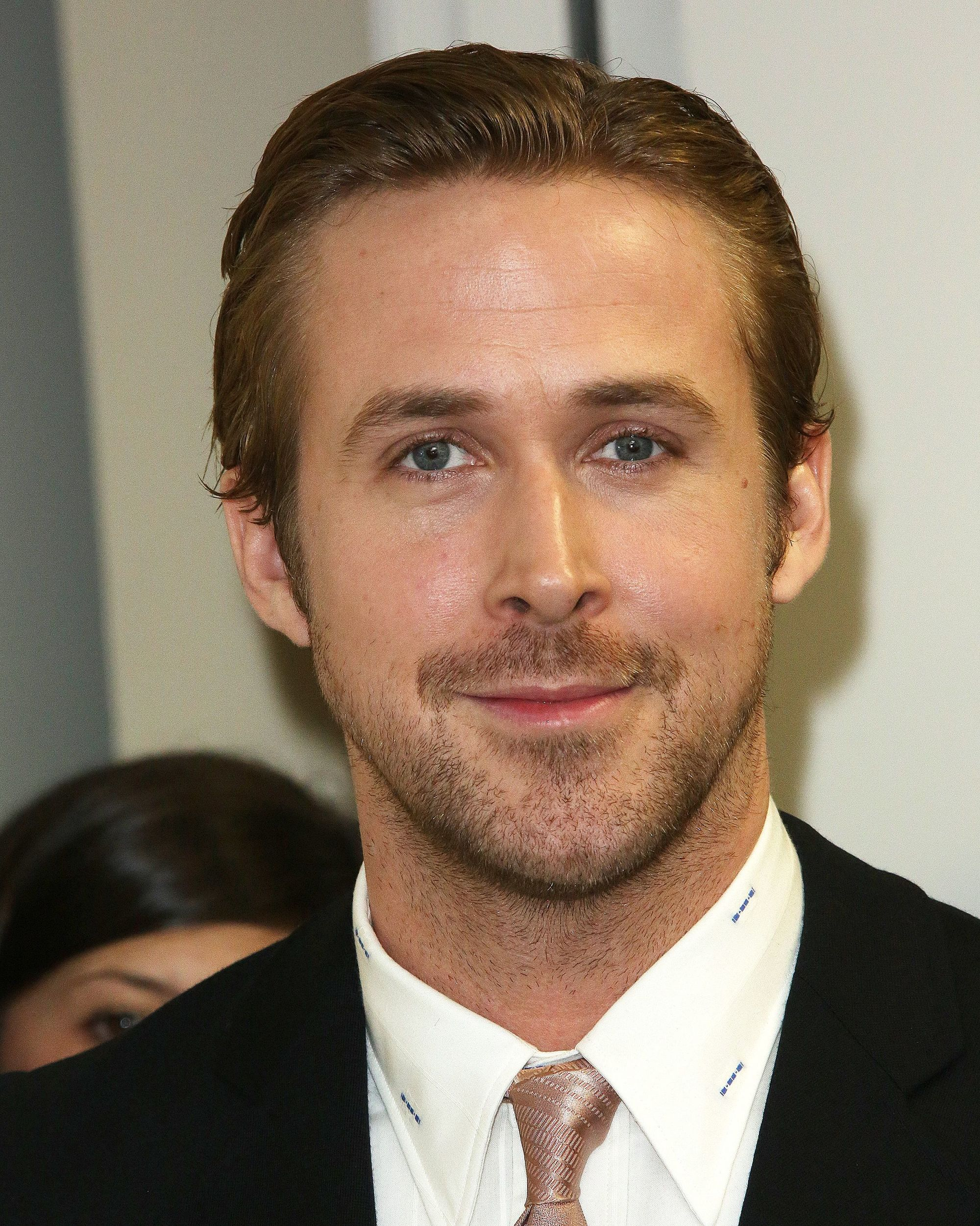 Ryan Gosling haircut: Ryan Gosling with a smart brushed back hairstyle, with short facial hair and wearing a suit and tie