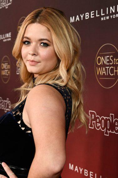 close up shot of sasha pieterse at the people's ones to watch party, wearing black dress and curly hair