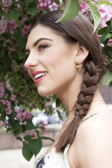 Side braid tutorial girl with brown hair outside smiling near purple flowers