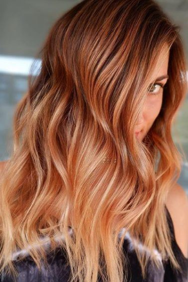 Spiced cider hair: Woman with long, wavy spiced cider pumpkin hair, wearing black and posing in a salon