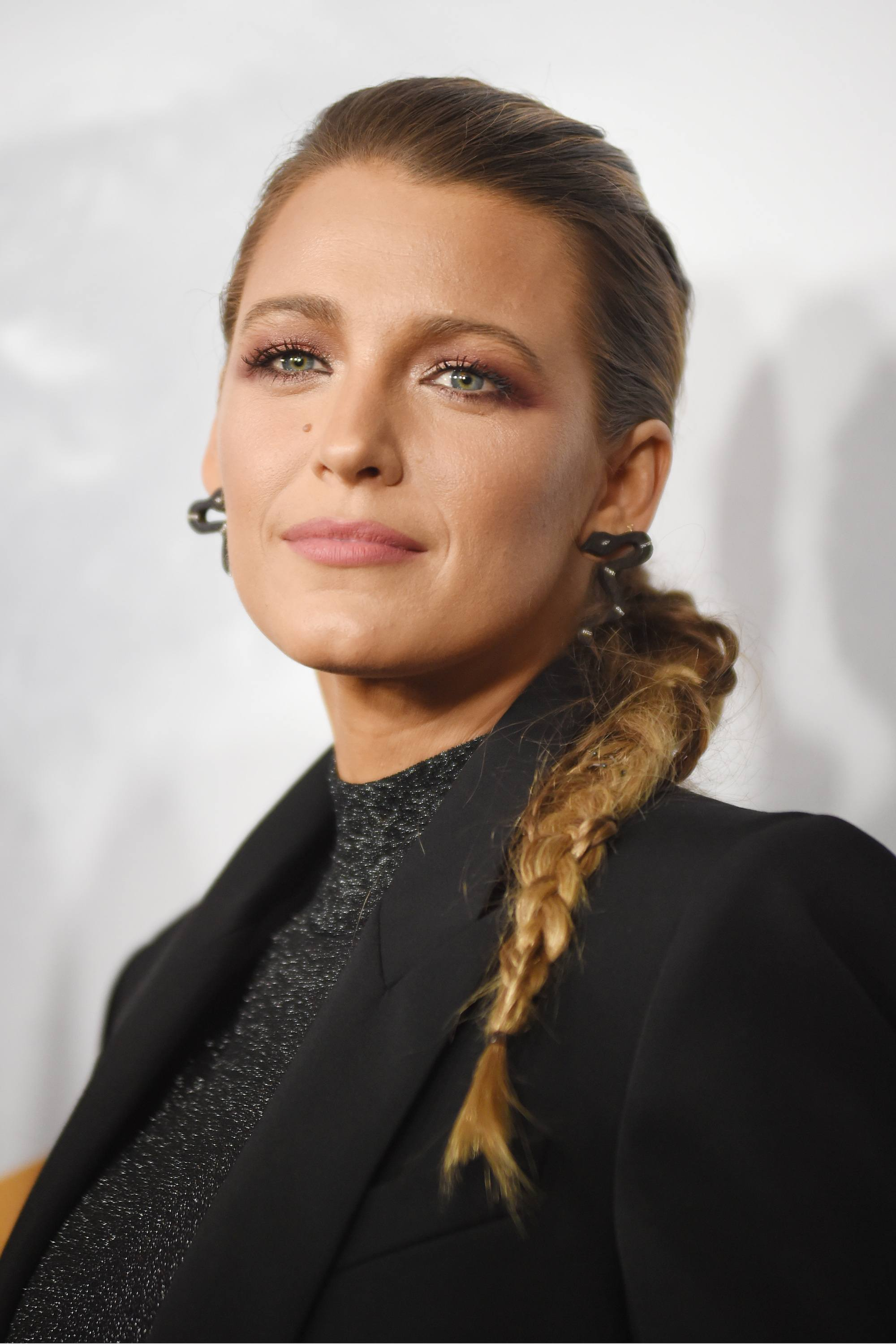 Blake Lively with golden blonde hair styled into a side braid, wearing all black on the red carpet