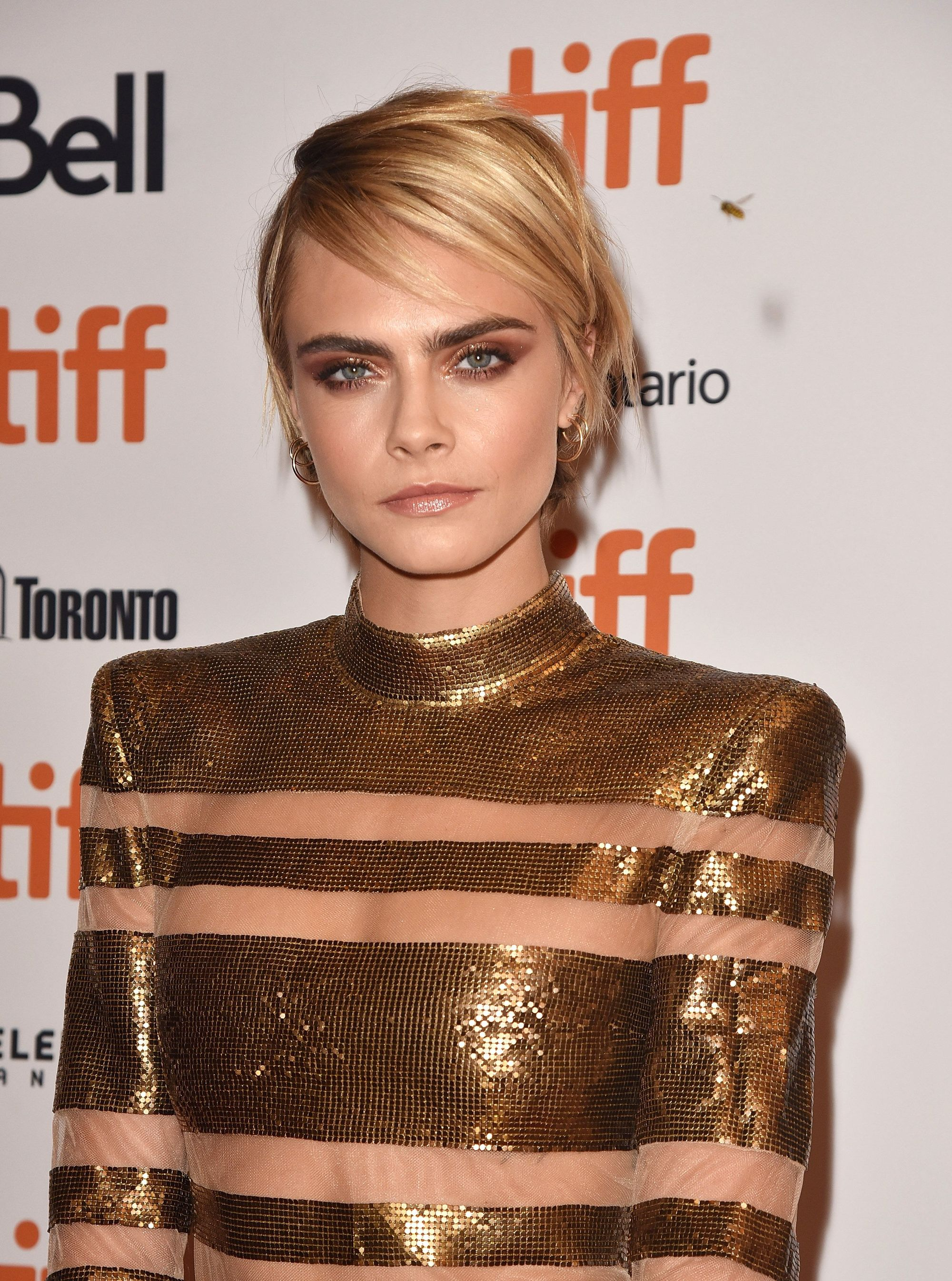 Cara Delevingne with short side-swept golden long pixie, wearing all gold on the red carpet