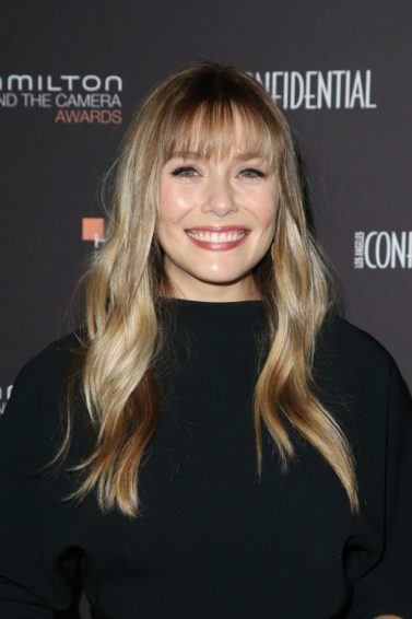 Elizabeth Olsen with long, wavy dirty blonde hair with long and straight feathery bangs, wearing all black on the red carpet