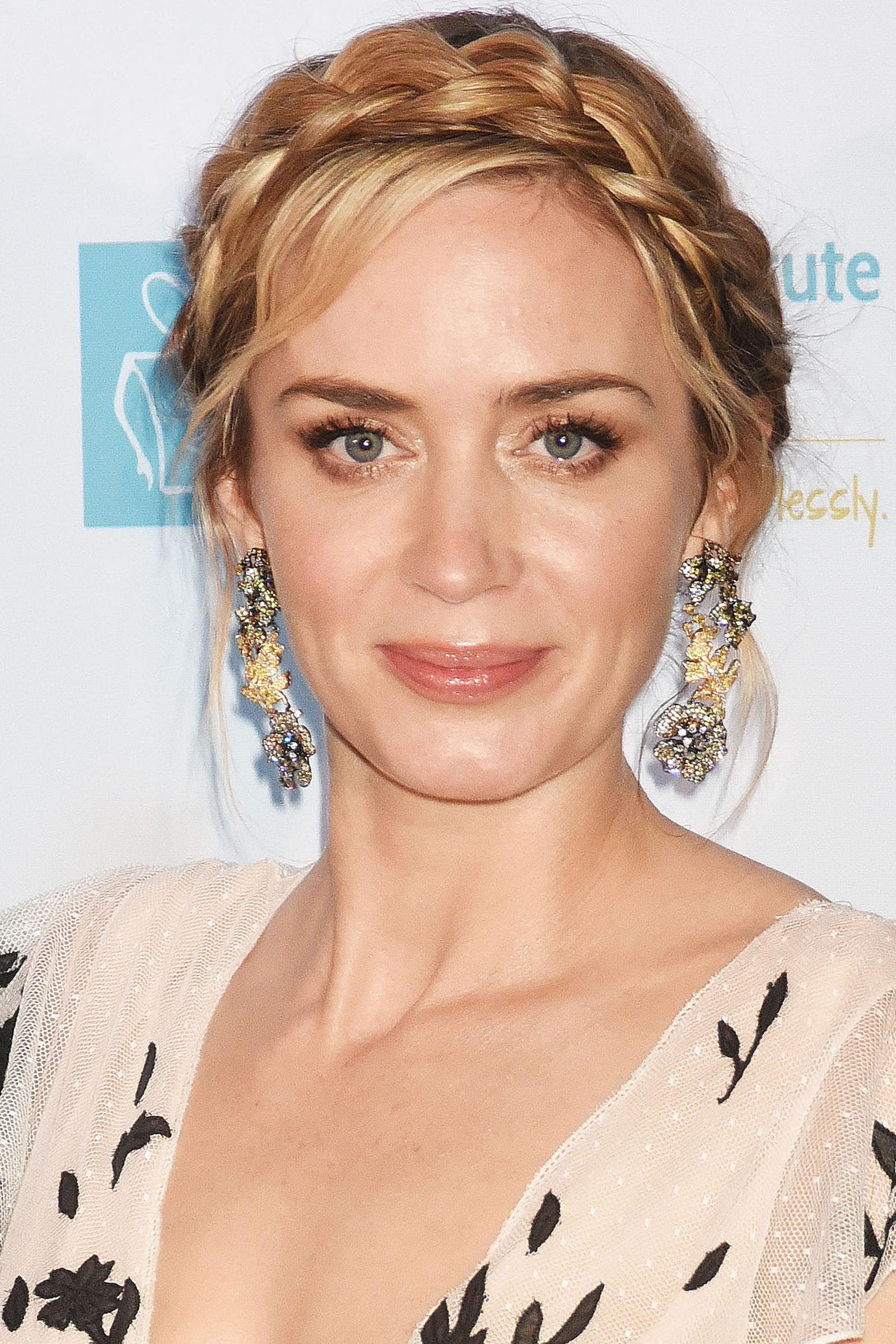 Emily Blunt with her golden blonde hair styled into a halo braid with wispy tendrils at the front, wearing pink dress and posing on the red carpet