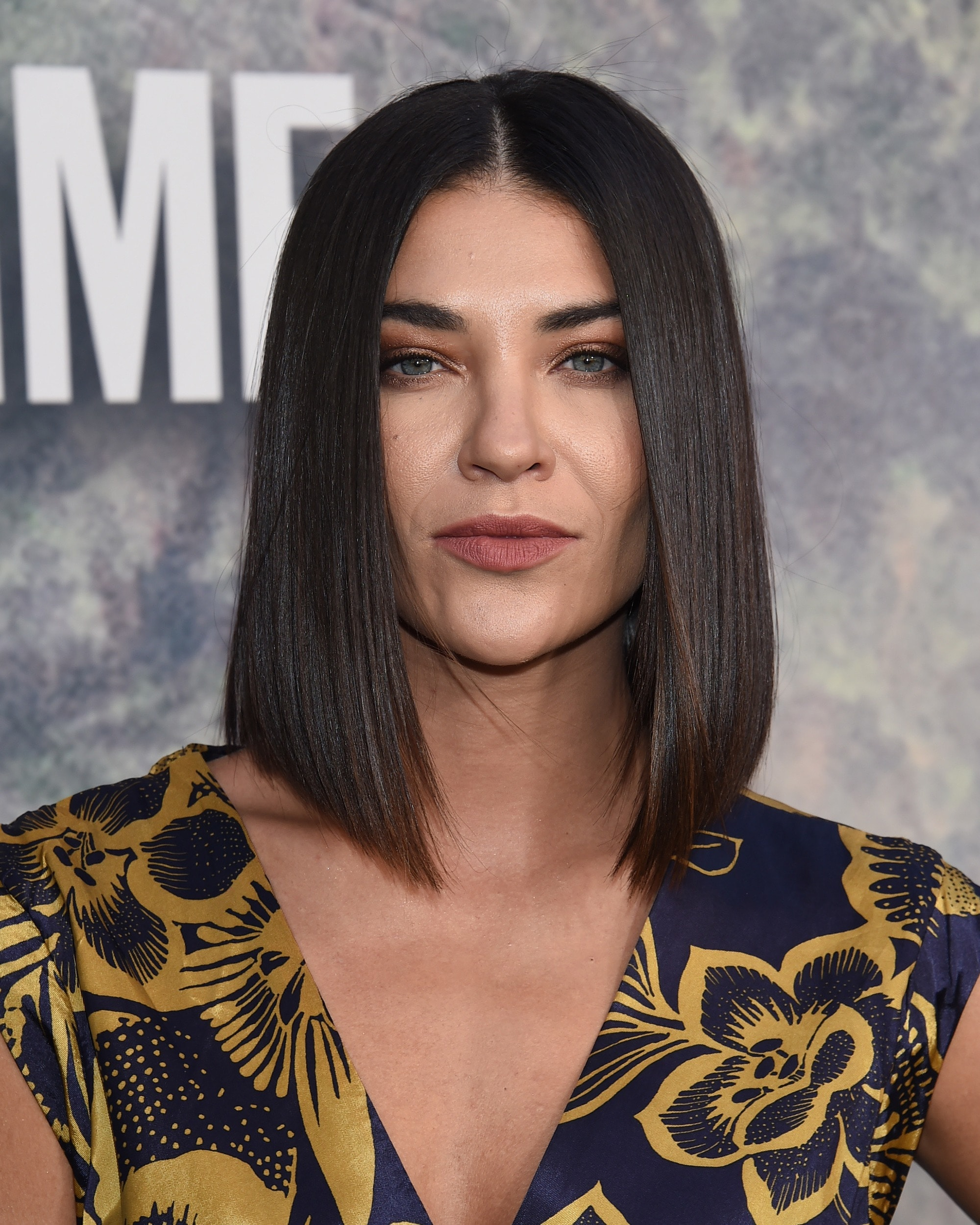 Jessica Szohr with medium dark brown hair styled into an angled blunt cut bob, wearing printed top on the red carpet
