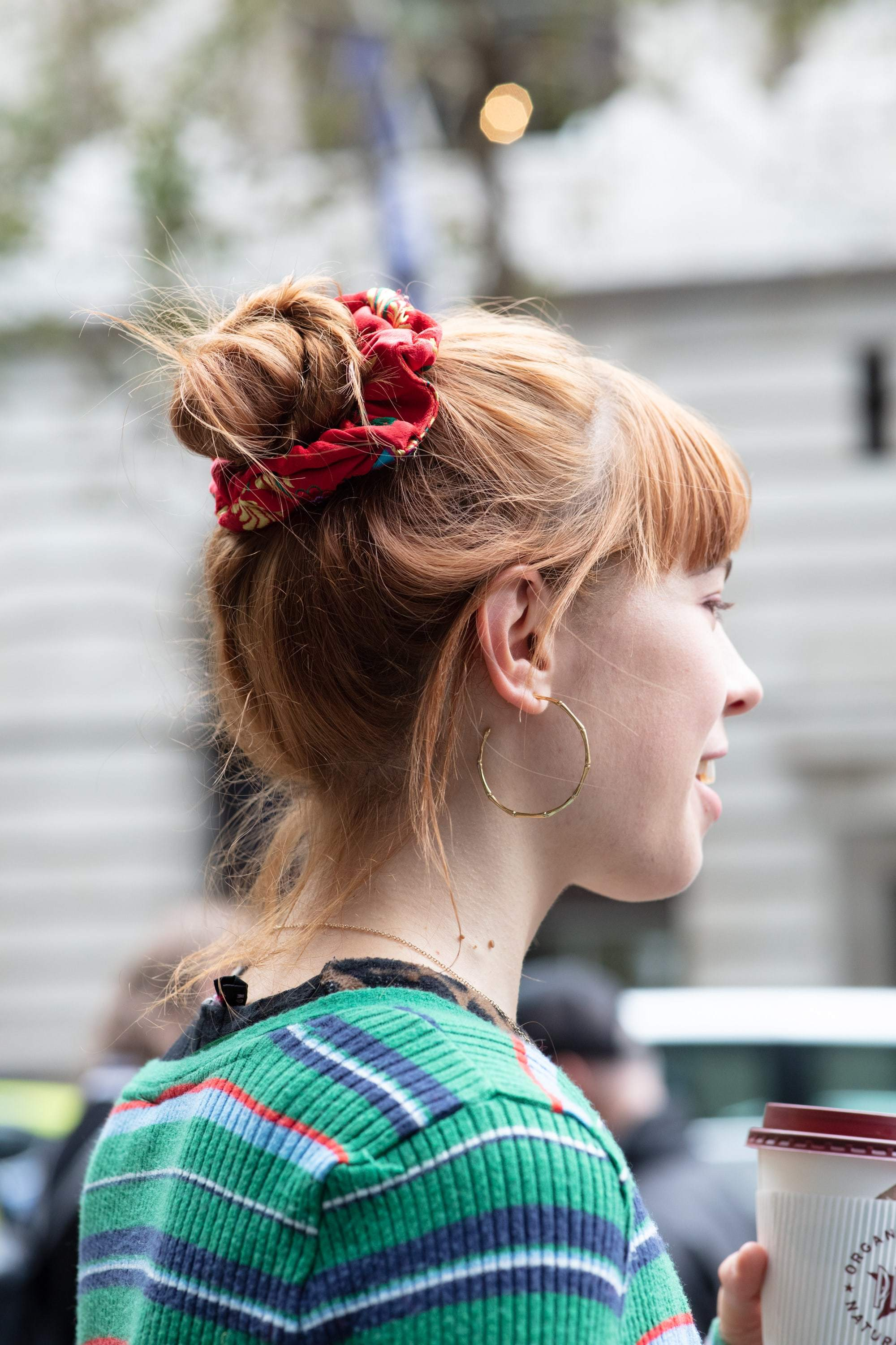 Woman with copper red fine hair styled into a messy bun with a scrunchie, wearing green striped top and posing for a street style all things hair shot