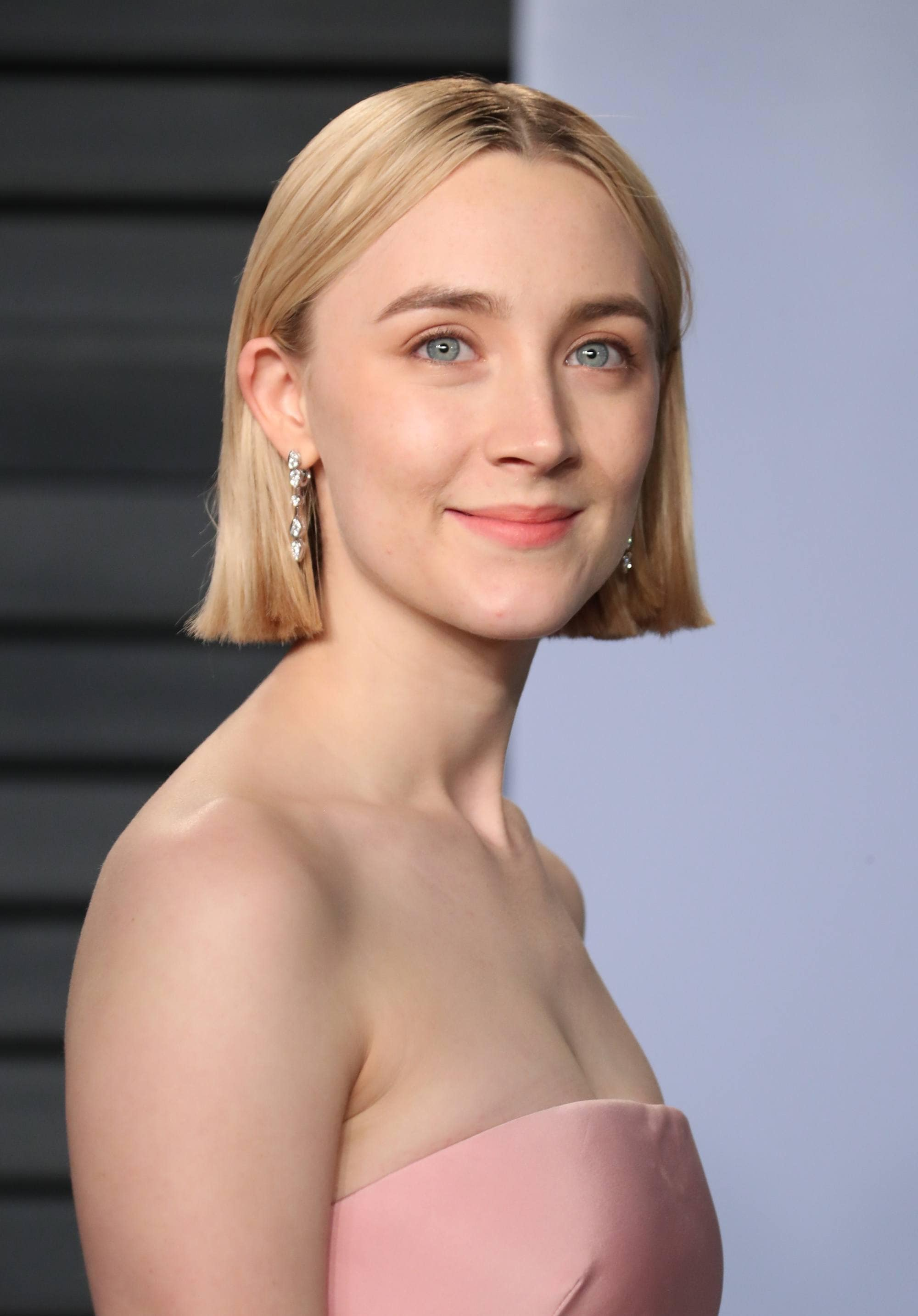 Saoirse Ronan with golden blonde blunt bob hair, with pink dress on the red carpet