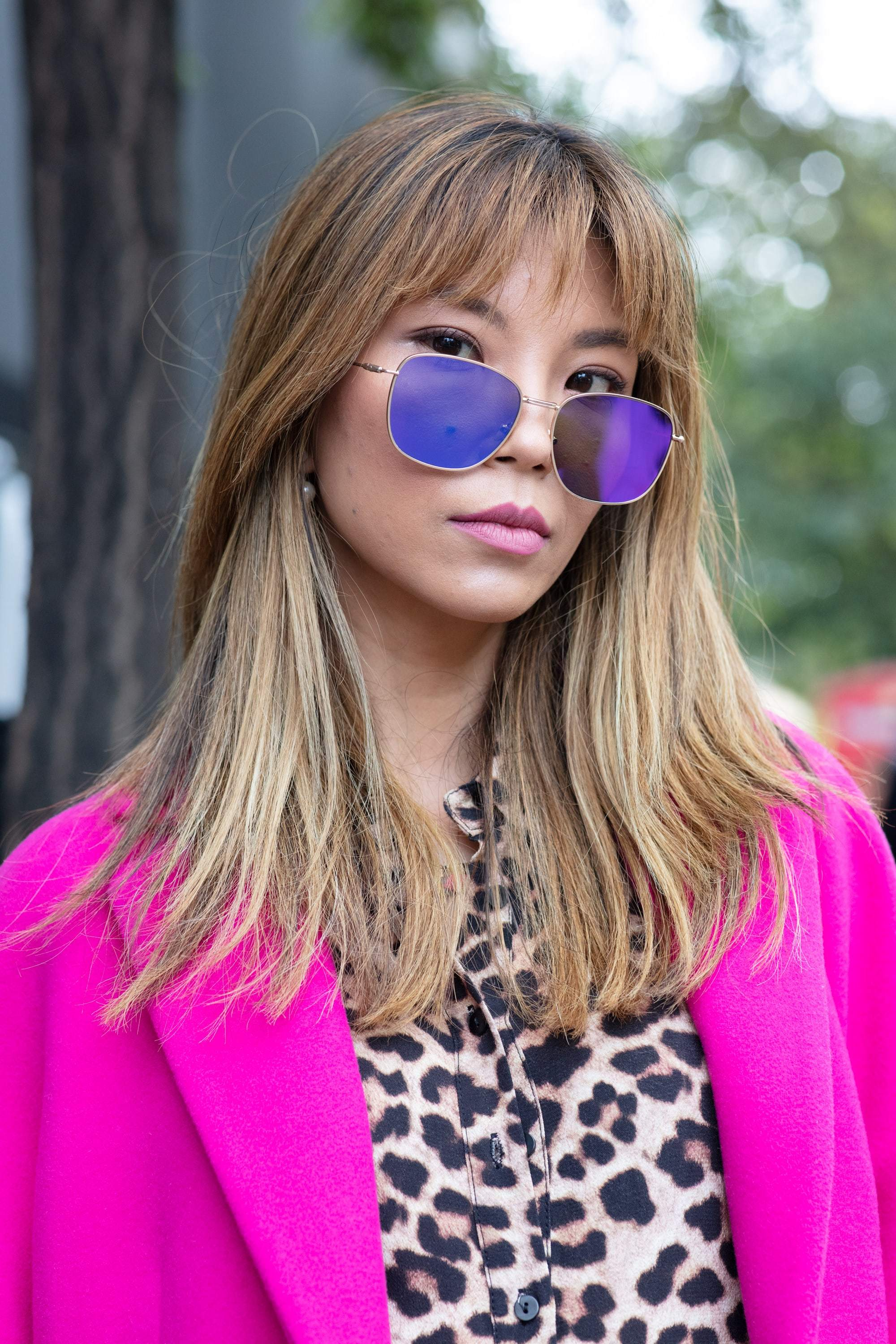 Shot of woman with dark blonde medium hair with sleek, feathery layers in it, wearing sunglasses with hot pink jacket