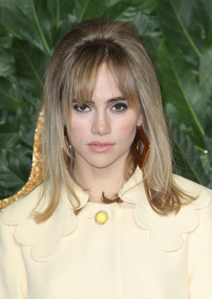 The Fashion Awards 2018: Suki Waterhouse with dark blonde shoulder length hair in a sixties inspired beehive hairstyle wearing a retro yellow coat dress