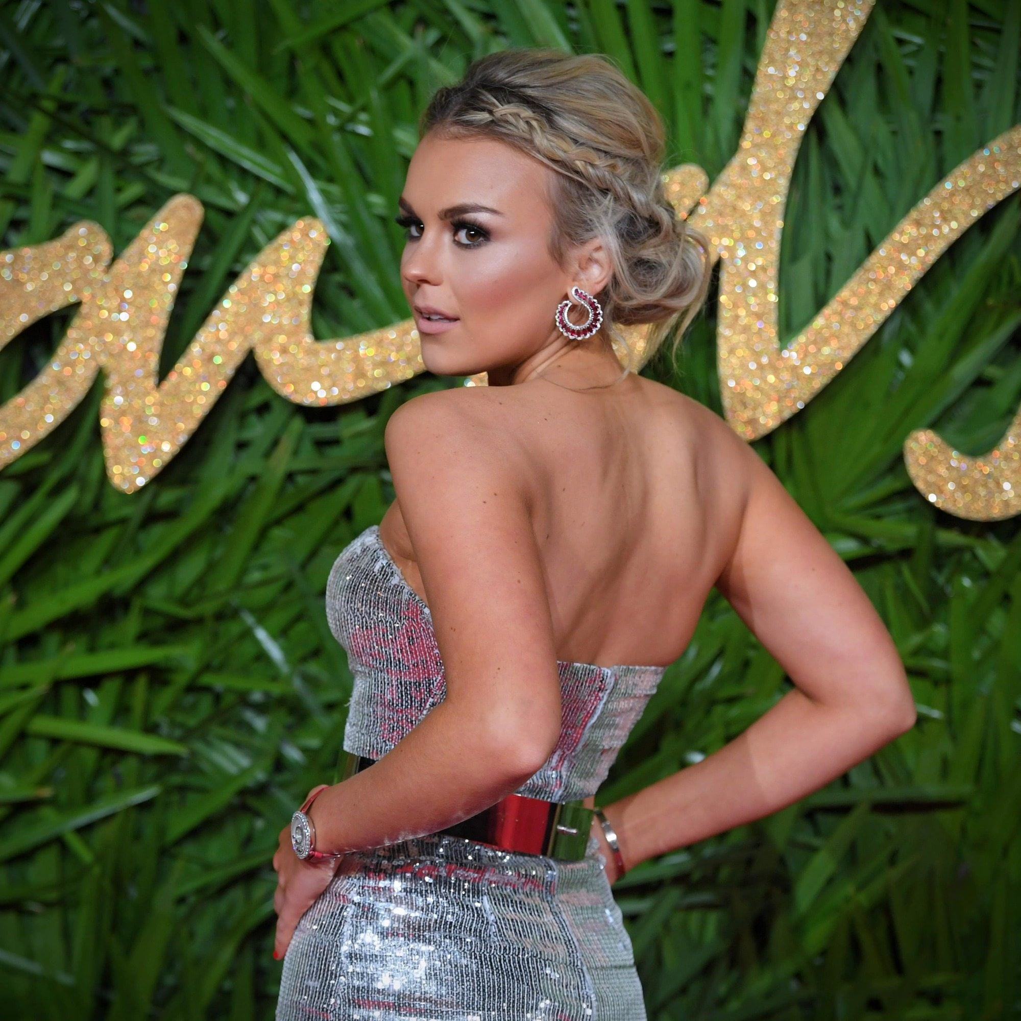 singer tallia storm at the british fashion awards in a sparkly silver dress with her hair in a plaited updo