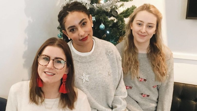 close up shot of three girls wearing christmas jumpers in a sitting room