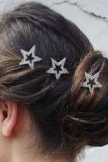 side view of a brunette woman with her hair in a twisted updo with star hair accessories