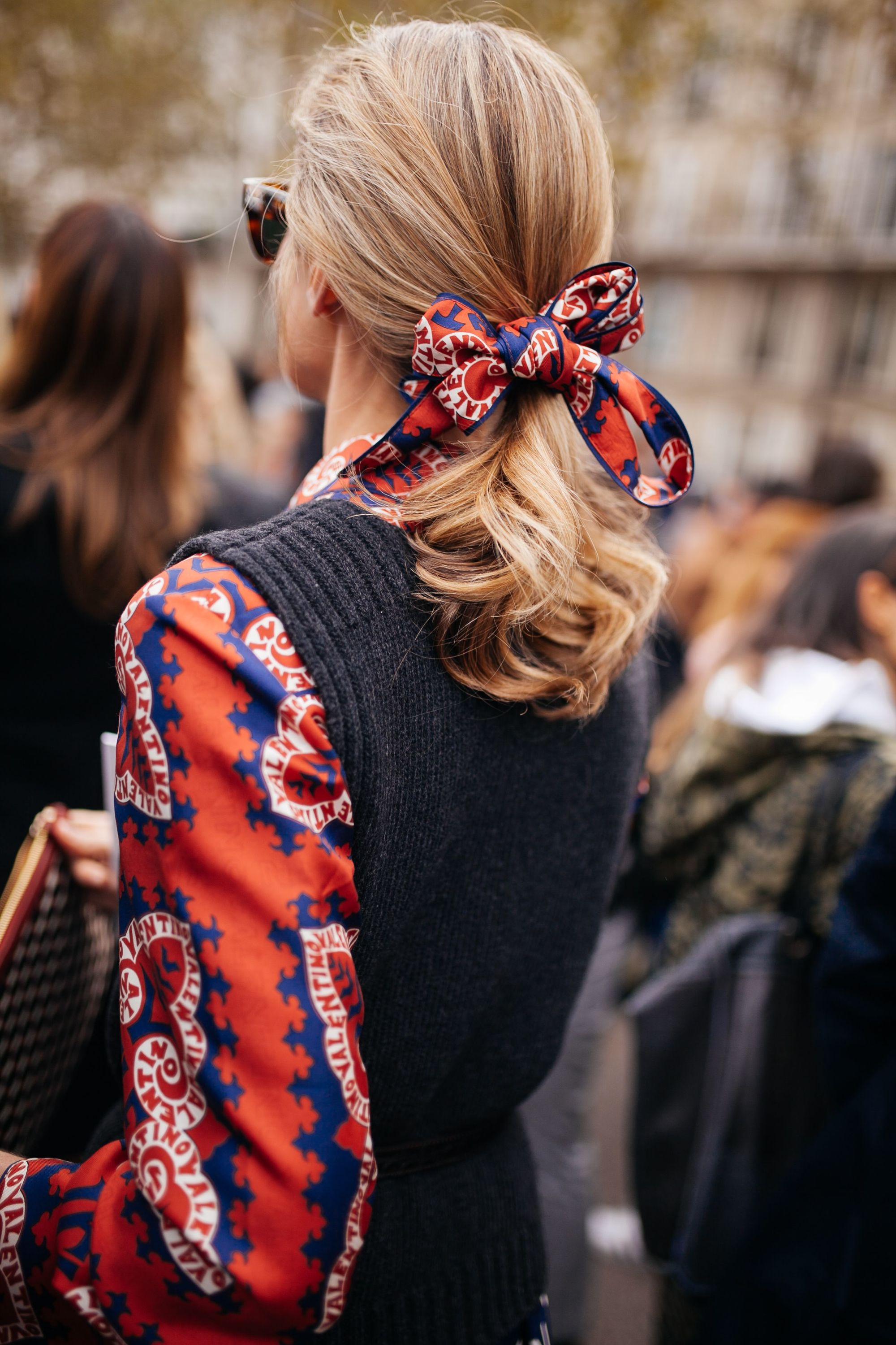 Backshot of woman with medium fine hair styled into a low voluminous ponytail, with hairscarf around it on the street
