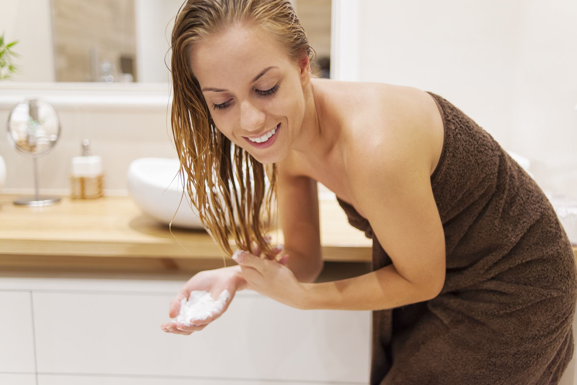 Woman with wet hair in brown towel about to put hair mousse into blonde hair