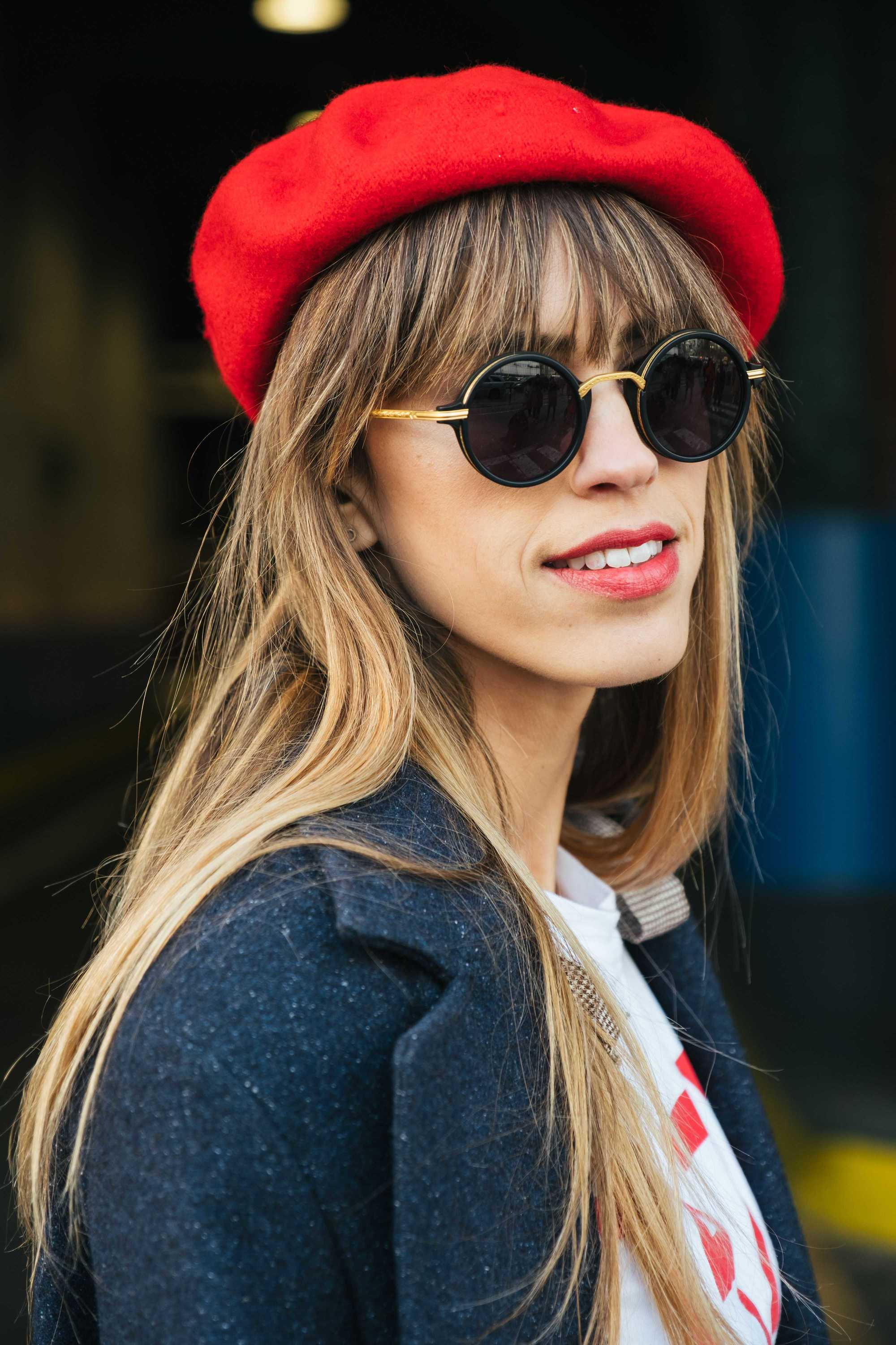 Haircut ideas for thin hair: Woman with honey brown long straight, fine hair with wispy straight bangs, wearing sunglasses and red beret