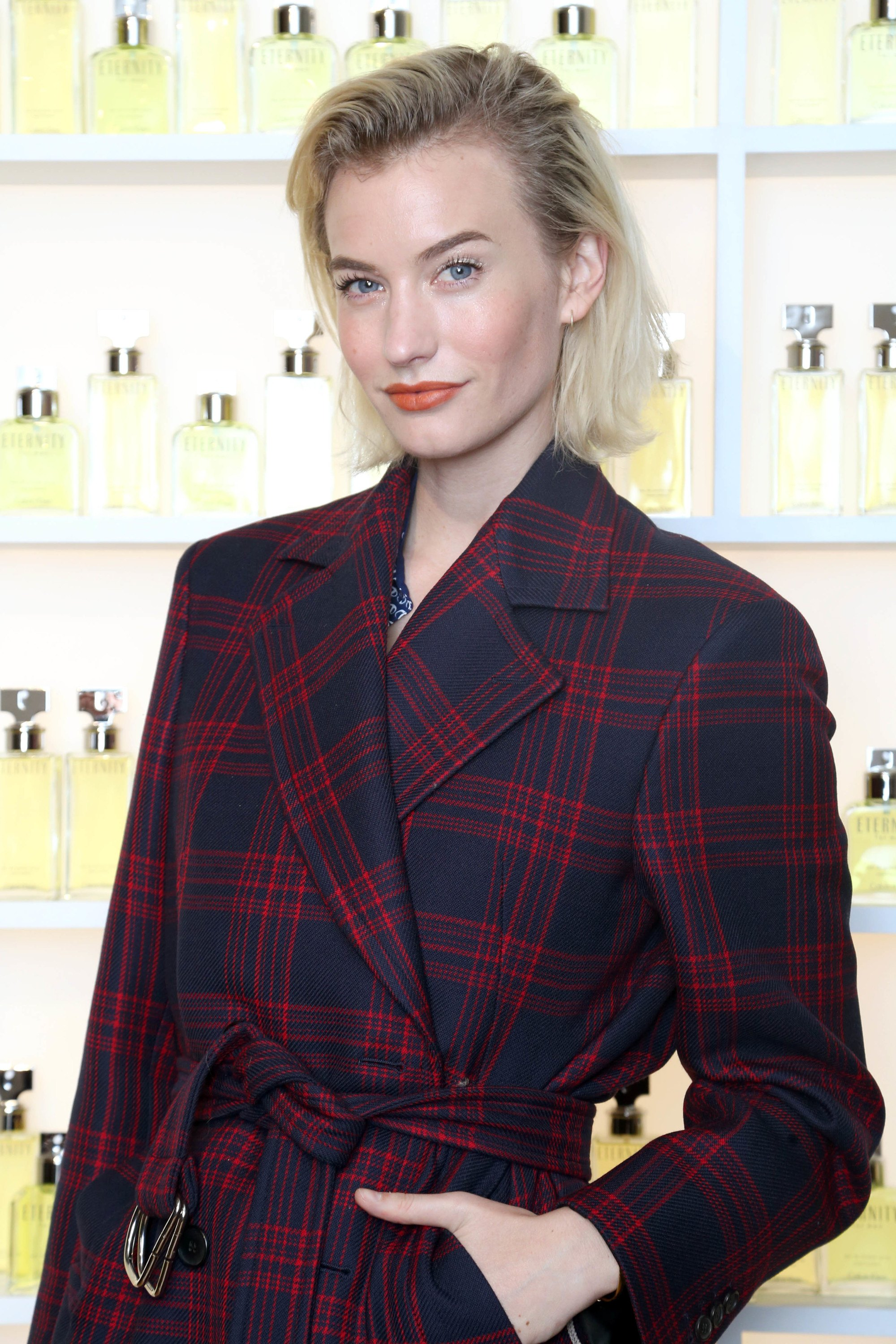 How to style thin hair: Zanita Whittington with fine platinum blonde hair styled into a swept-back slick hairstyle, wearing tartan jacket on posing on the red carpet